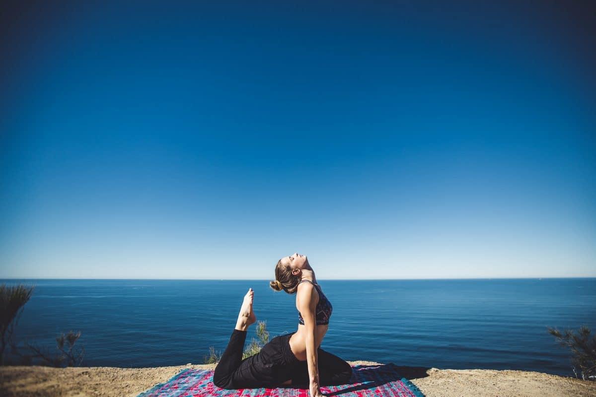 žena cvičící jógu u moře