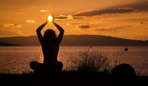 žena cvičí jógu u vody